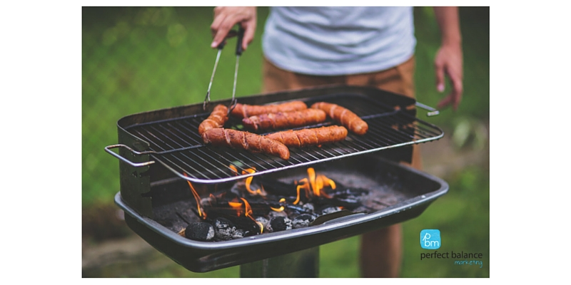 man cooking sausages on barbecue